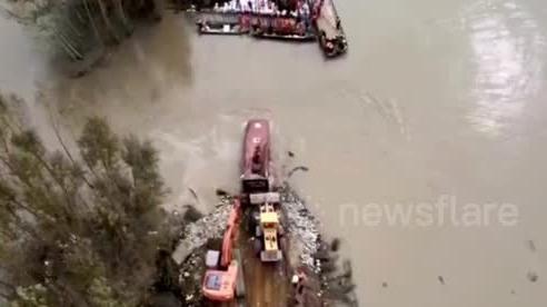 Xe buýt chứa đầy đá và bùn bị đẩy xuống sông lấp đê vỡ ở Trung Quốc
