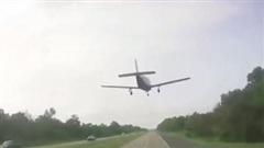 Clip máy bay đáp trước mũi xe ô tô trên đường cao tốc
