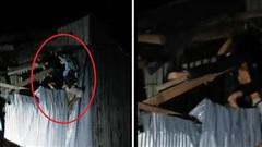 Hiện trường tai nạn đáng sợ: 2 thanh niên chạy xe máy, bay lên nóc nhà bên đường, mắc kẹt