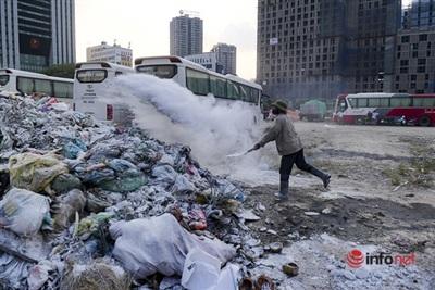 ÔngLại Văn Phúc rắc vôi bột lên bãi rác tạm.