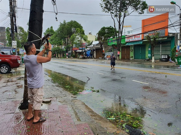 Người dân đứng trước cửa nhà chụp hình quang cảnh tan hoang do bão (Ảnh: Văn Tiên)