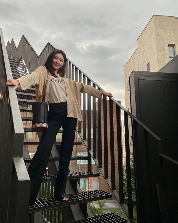 Soo Young khoe đôi chân dài triệt để với quần ống suôn sơ vin cao lên eo. Cô phối đơn giản với áo phông được sơ vin trong quần và bên ngoài là áo cardigan mỏng nhẹ, mát mẻ.