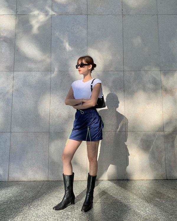 Mai Anh chứng minh khả năng bắt trend nhanh nhạy khi phối áo phông trắng cùng chân váy dây rút thời thượng. Loạt item như kính mắt, túi xách và boots da chính là bí quyết để set đồ của cô nàng trở nên chất chơi sành điệu hơn.