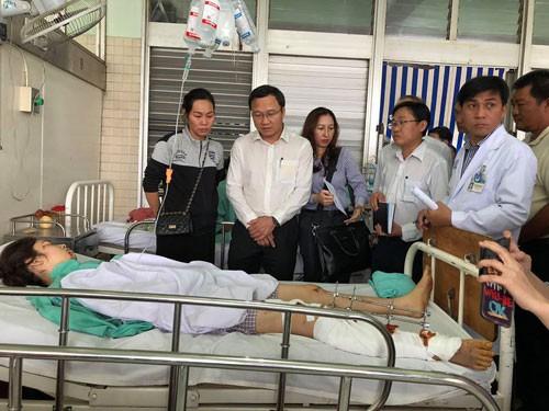 Ông Khuất Việt Hùng (thứ hai từ trái qua) thăm hỏi các nạn nhân tại Bệnh viện Chợ Rẫy (TP HCM) Ảnh: TRỊNH THIỆP.