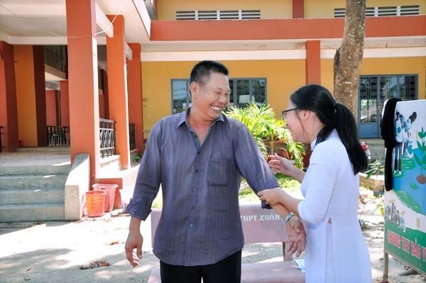 Người cha trong bộ quần áo giản dị, lấm tấm mồ hôi vẫn nở nụ cười rạng rỡ chụp ảnh cùng con gái.