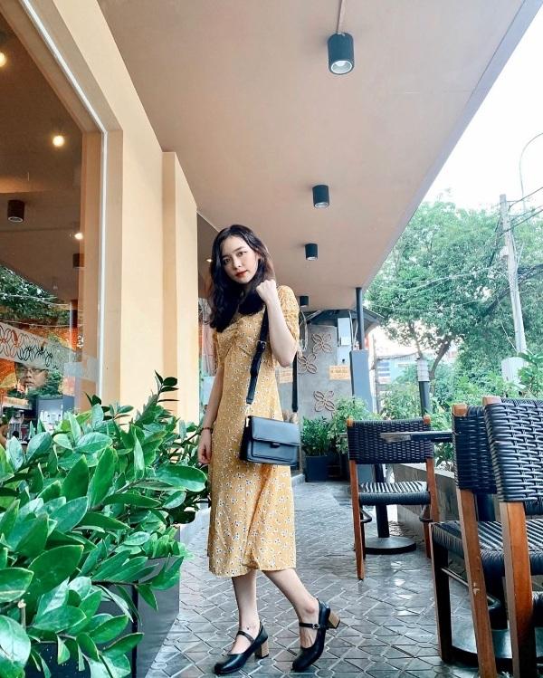 Đinh Ngọc Phi Linh xinh xắn, ngọt ngào với bộ cánh nhẹ nhàng đậm chất vintage. Lựa chọn cho mình một thiết kế đầm hoa nhí phủ sắc vàng tươi tắn, cô kết hợp trang phục cùng túi xách và giày cao gót tiệp màu đen.