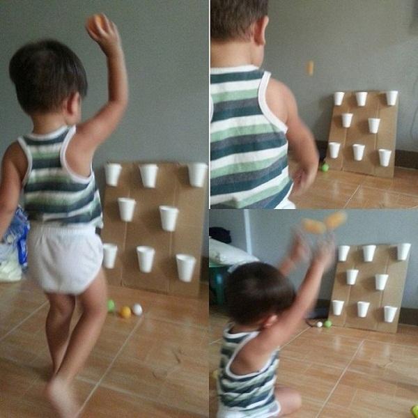 Mẹ trẻ tự làm bảng cốc giấy cho con chơi trò ném bóng vào cốc. (Ảnh: Lucas)