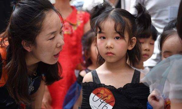 Người mẹ đang động viên con gái mình trước khi em bước lên sàn diễn của một cuộc thi tìm kiếm mẫu nhí.
