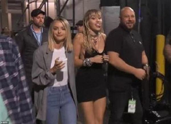 Nữ ca sĩ được Kaitlynn Carter hộ tống sau cánh gà.
