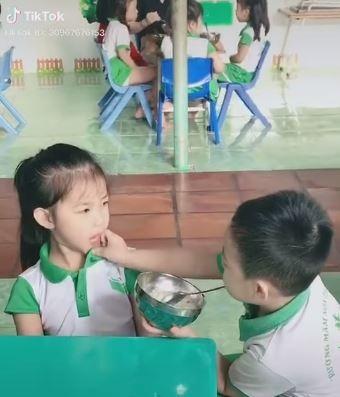 Không những bón cơm, bé trai còn lau miệng bẩn cho bé gái. Ảnh cắt màn hình.