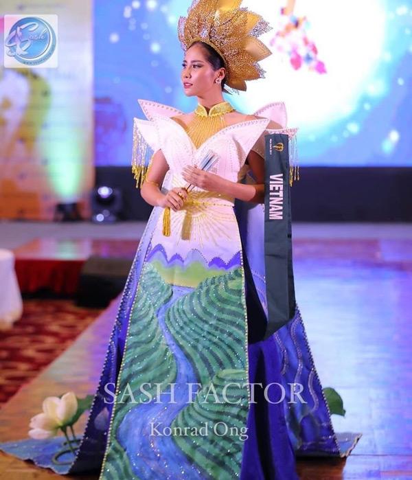 Quốc phục Việt Nam đính 5000 viên pha lê, tà trước vẽ tay phong cảnh Tây Bắc hùng vĩ, tà sau dựng 3D cả hồ sen. Màu sắc quốc phục trắng xanh rất hiện đại, nổi bật dưới ánh đèn sân khấu, chiếc mấn vàng hình hoa sen cũng tôn lên vẻ đẹp trang phục.