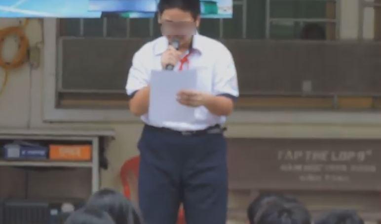 Nam sinh đứng trước trường đọc bản kiểm điểm về hành vi của mình.
