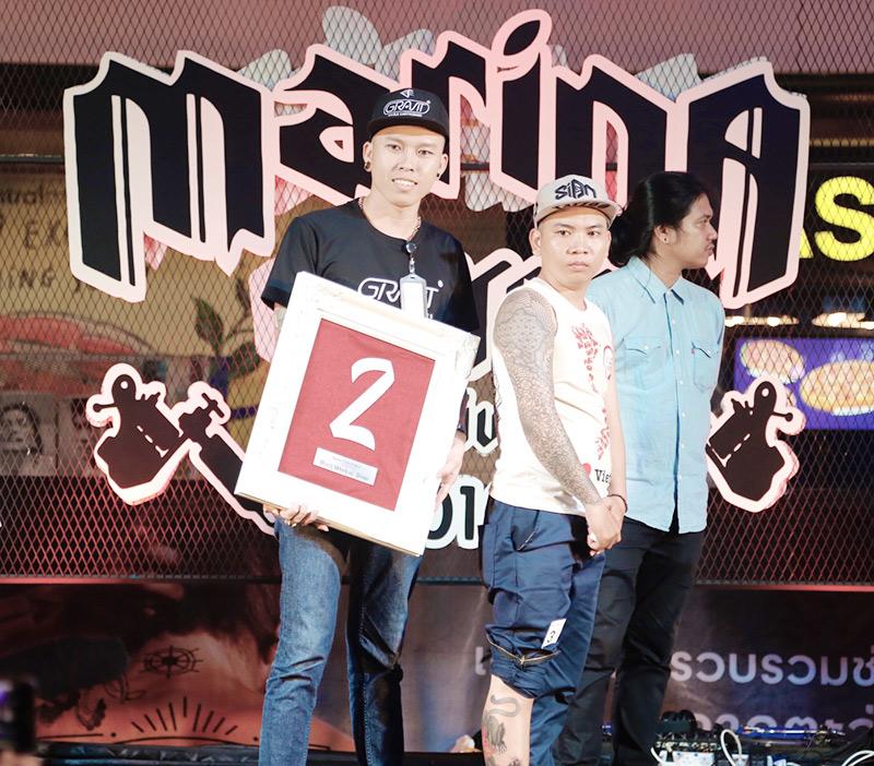 Thợ xăm trẻ Dương Thanh (trái) và giải thưởng vừa nhận được tại cuộc thi xăm quốc tế.