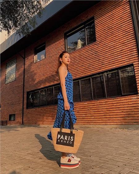 Chi Pu theo đuổi style nữ tính với chiếc đầm chấm bi xanh, nhún bèo duyên dáng. Người đẹp tạo điểm nhấn cho set đồ bằng chiếc túi cói Kenzo và đôi giầy đế xuồng Gucci.