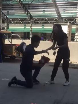 Chàng trai ra sức tặng hoa còn cô gái ra sức kéo bắt đứng lên. Ảnh cắt từ clip.