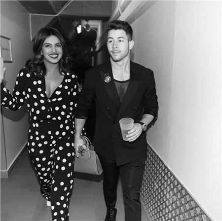 Cặp đôi Nick Jonas and Priyanka Chopra đã chia sẻ khoảnh khắc ngọt ngào bên nhau trên mạng xã hội. Trong ảnh, Chopra mặc bộ jumpsuit chấm bi dễ thương trắng, đen còn Nick mặc chiếc áo vest đen cách điệu bên ngoài lớp áo lưới mỏng, tay áo được xắn lên để thêm phần phong cách.