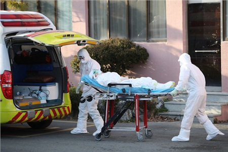 Các nhân viên y tế di chuyển một người nghi nhiễm COVID-19 ở Bệnh viện Daenam ở Cheongdo - Ảnh: REUTERS