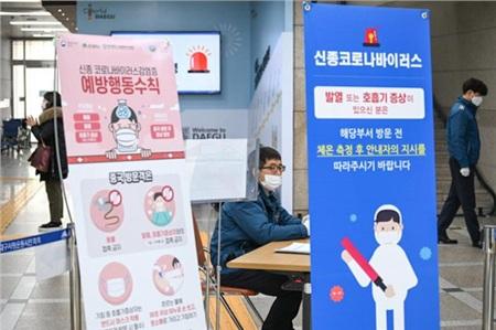 Bảng cảnh báo dịch COVID-19 và máy quét nhiệt tại một tòa nhà công ở Deagu - Ảnh: UPI