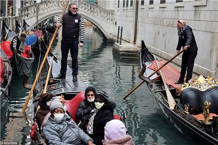 Khách du lịch đeo khẩu trang bảo vệ trong một chiếc thuyền tham quan kênh đào ở Venice, vì sự bùng phát của virus Corona