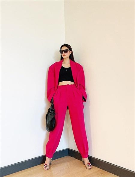 Cách mix nguyên bộ suit hồng cánh sen cùng áo crop-top đen bó sát làm bộ đồ trở nên bắt mắt. Hoa hậu Phạm Hương trông cực nổi bật với gu thời trang 'sang chảnh' này.