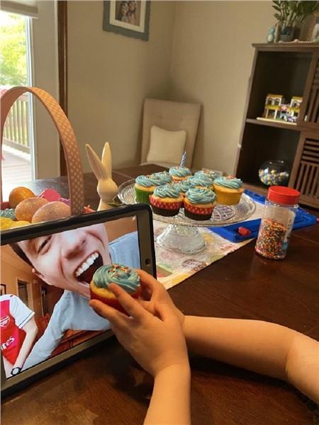 Con gái tôi đang mời emtrai tôiăn bánh cupcake qua video call.