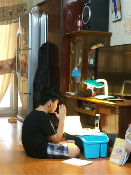 Cậu bé đang tập trung học trực tuyến tại nhà và không quên giơ tay phát biểu ý kiến như ở trên lớp.