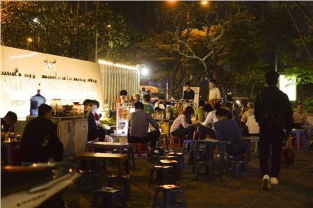 Khung cảnh đông vui, tấp nập tại một quán trà đá trên đường Phạm Văn Bạch (quận Cầu Giấy, Hà Nội) ngay trước tấm biển Việt Huyết học - Truyền máu Trung ương vào đêm 26/3.