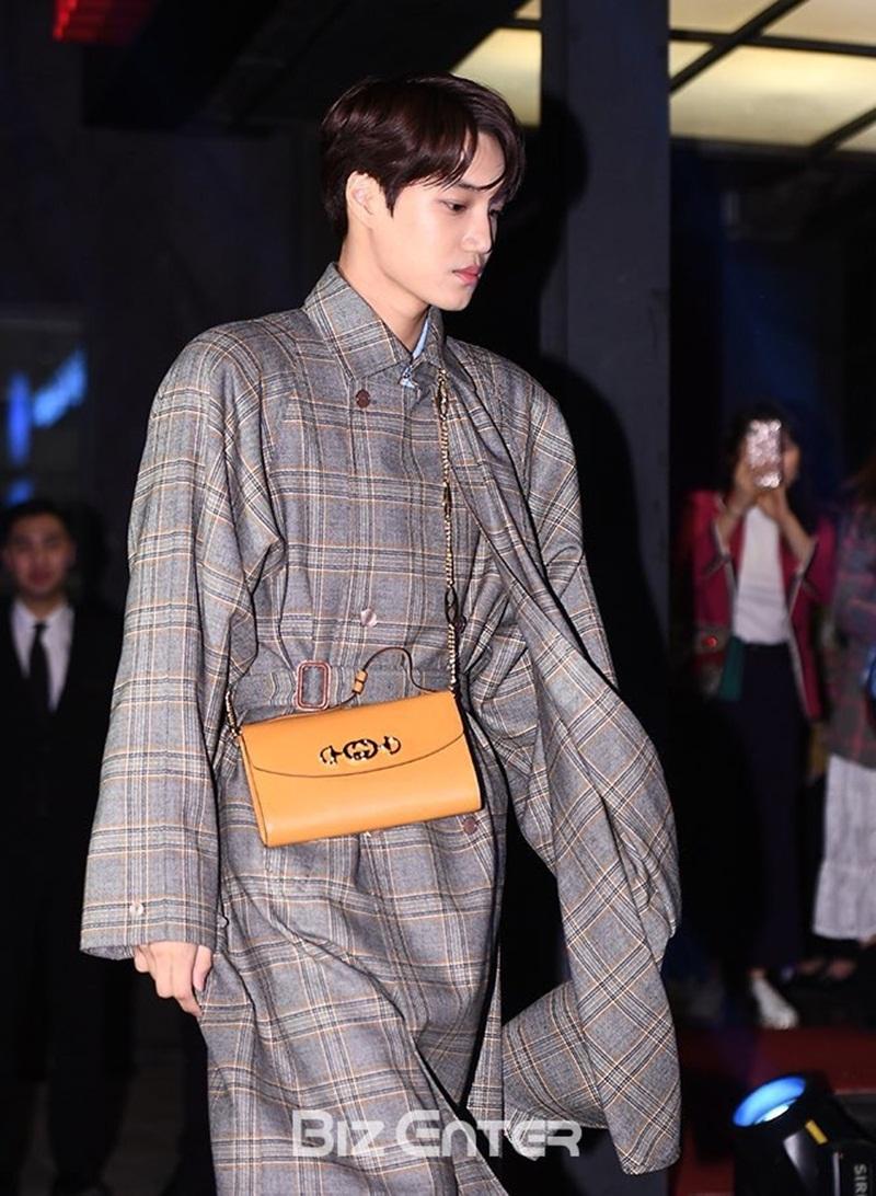 Chiếc túi có thiết kế hình chữ nhật được bo tròn tất cả các góc cạnh. Sợi quai chéo mạ vàng đã trở thành điểm nhấn cho bộ trang phục của Kai.