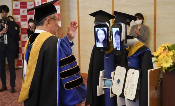 Thầy hiệu trưởng tụ tay trao bằng cho các robot có hình ảnh mặt sinh viên đang theo dõi buổi lễ qua trực tuyến.