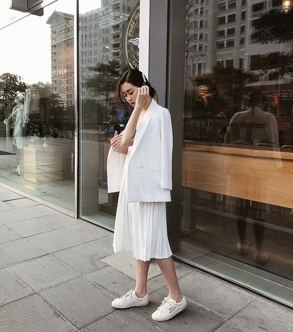 Ngoài diện cả cây đồ đen, Tường San còn thường xuyên diện những set đồ xuyệt tông trắng. Vẫn với bộ đôi blazer và chân váy xếp ly midi nhưng thay vì giày cao gót, thì cô lại mix trang phục cùng sneaker nhằm tạo sự năng động trẻ trung cho hình ảnh.