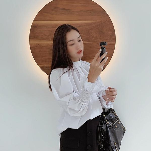Đối với nàng công sở mà nói, chỉ cần lên đồ đơn giản như Tường San với áo blouse trắng mix với chân váy đen, nhấn nhá thêm chiếc túi xách da đồng điệu về màu sắc này thôi là đủ hoàn thiện vẻ thanh lịch cần có rồi.