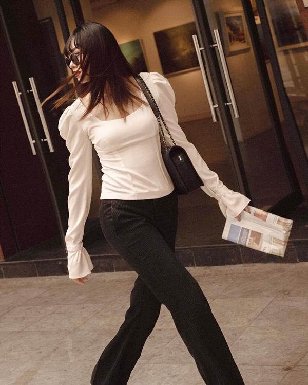 Vẫn trung thành với 2 gam màu đen trắng kinh điển nhưng khi diện cặp đôi quần tay ống đứng và áo tay loe cổ vuông, cô nàng trông hiện đại và năng động hơn.