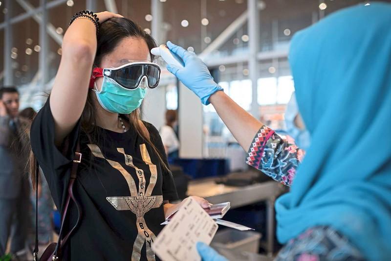 Một nhân viên hàng không của hãng Malaysia Airlines đo nhiệt độ một hành khách Trung Quốc tại sân bay quốc tế Kuala Lumpur. Ảnh: AFP