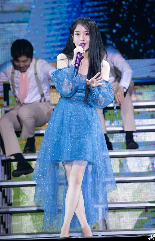 Trên sân khấu, IU luôn khiến khán giả bất ngờ và trầm trồ khi diện những bộ cánh công chúa dịu dàng như chiếc váy xanh cách điệu vạt trước ngắn. Thiết kế điệu đà, nữ tính có chất liệu mềm mại này thật sự rất hợp với cô nàng 'bánh bèo'.