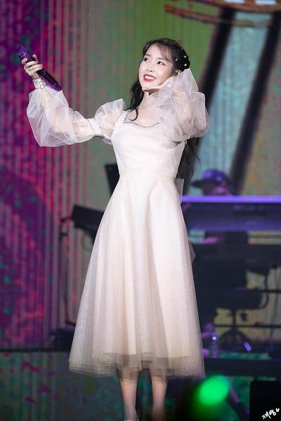 Sở hữu ngoại hình nhỏ nhắn cùng gương mặt trong trẻo, 'em gái quốc dân' thường xuyên xuất hiện với những mẫu váy dài, chiết eo, tay phồng với màu sắc tươi sáng. Chẳng hạn như chiếc váy hồng nhạt có tay bồng bềnh được cô lựa chọn khi bước lên sân khấu, giúp cô như một thiên thần trong mắt người hâm mộ.