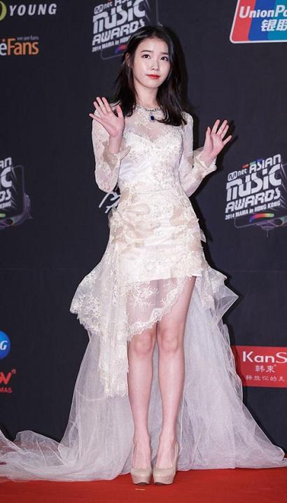 Lộng lẫy trong bộ đầm ren trắng, IU trông như một cô dâu xinh đẹp đang thả dáng trước ống kính của thảm đỏ vậy. Cô gái đa tài đã khoe trọn đôi chân dài thon gọn và bao nét quyến rũ, tinh tế của mình.