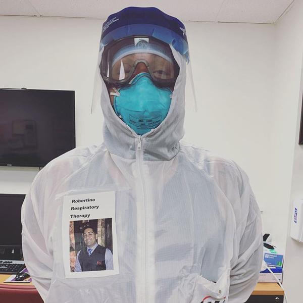 Bác sĩ Robertino trong bộ đồ bảo hộ có dán ảnh tươi cười của mình để trấn an tinh thần các bệnh nhân.