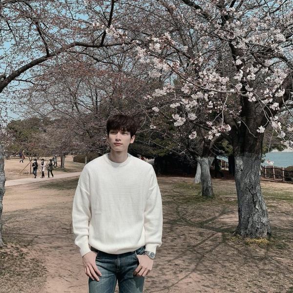Chụp ảnh bên hoa cỏ thì nhất định phải mặc đồ màu sáng để xinh tươi như hoa, như Hyuk (VIXX) lịch lãm, nhẹ nhàng trong chiếc áo len trắng dưới đây.