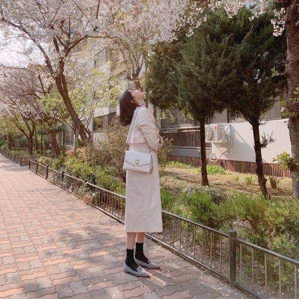 Kwon Nara ngắm hoa anh đào với set đồ nude nhẹ nhàng, thanh lịch gồm áo choàng dáng dài, túi đeo vai trắng, giày loafer. Sử dụng một tông trắng cho phần trên nhưng set đồ của Nara không bị 'ngộp' vì chọn nhiều sắc trắng phối hợp với nhau.