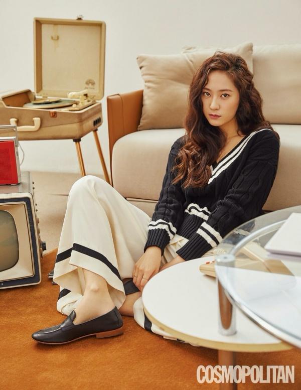 Krystal mặc thanh lịch, hiện đại với áo len cổ tim, quần ống rộng màu be họa tiết kẻ ngang.