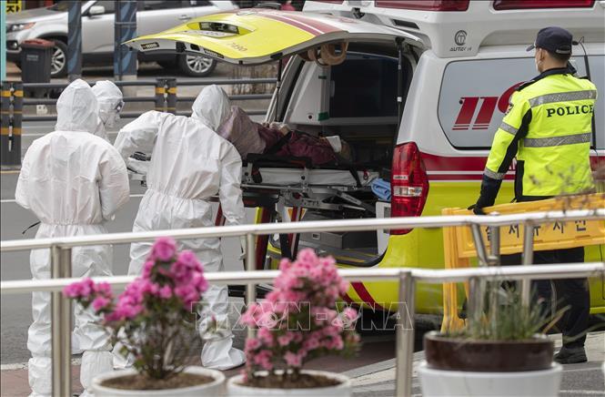 Nhân viên y tế chuyển bệnh nhân mắc COVID-19 tới bệnh viện ở thành phố Daegu, Hàn Quốc, ngày 19/3/2020. Ảnh: THX/TTXVN.