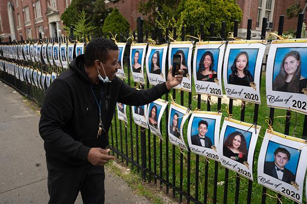Ồng Martin Philipchụp ảnh bức tranh con gái mình,Jessica, một trong 750 học sinh cuối cấp tại trường trung học James Madison ở Brooklyn, người đang được vinh danh trên hàng rào của trường.