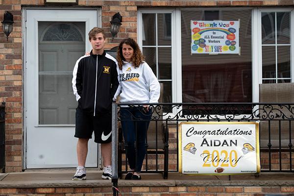 Cô Jodie Cohen vàcon traiAidan đứng trước cổng nhà, nơi treo những tấm biển lớn chúc mừng ngày tốt nghiệp của Aidan.