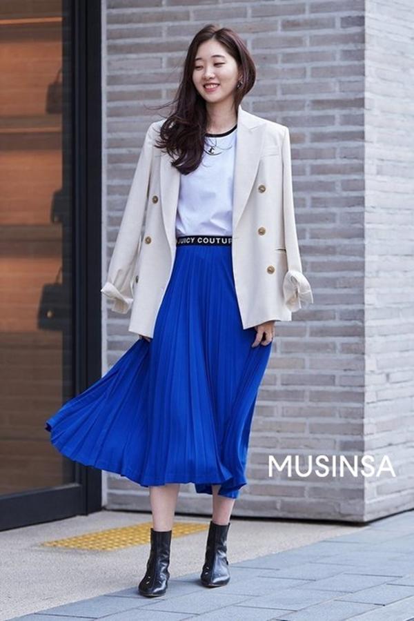 Set áo phông + chân váy xếp ly dịu dàng được cô bạn này nâng tầm phong cách với blazer dáng oversize màu be và một đôi boots ngắn cổ cá tính.