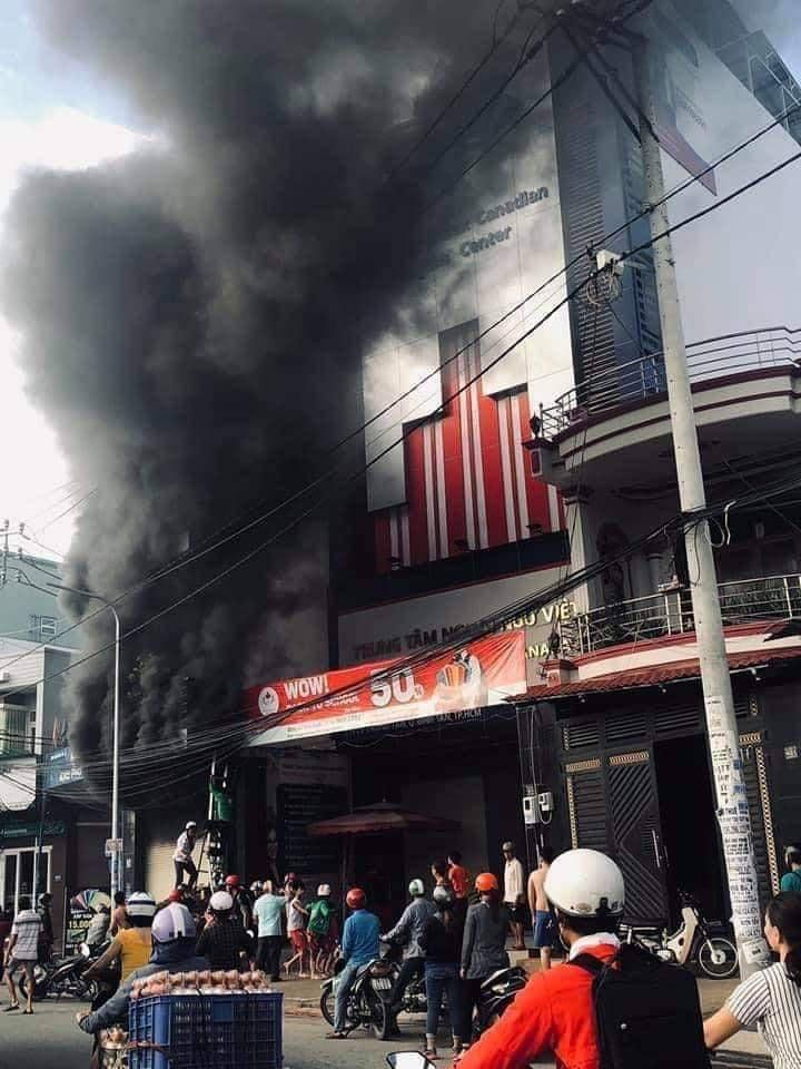 Nhiều người xung quanh đứng theo dõi quá trình chữa cháy.