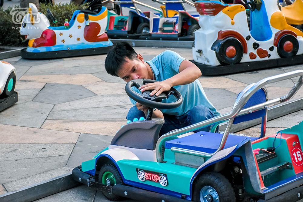 Một chủ hàng tranh thủ kiểm tra lại thiết bị, đồ chơi trước giờ cho khách thuê. Với mức phí từ 15-20k những dịch vụ giải trí này vẫn không được trẻ em thành phố tỏ ra hứng thú.