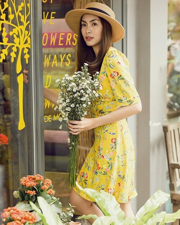 Bà xã Louis Nguyễn tươi tắn rạng ngời trong một thiết kế váy hoa nhỏ xinh mang sắc vàng của nắng. Thiết kế váy nhẹ nhàng đơn giản được bà mẹ hai con nâng tầm bằng phụ kiện mũ cói đậm chất vintage.