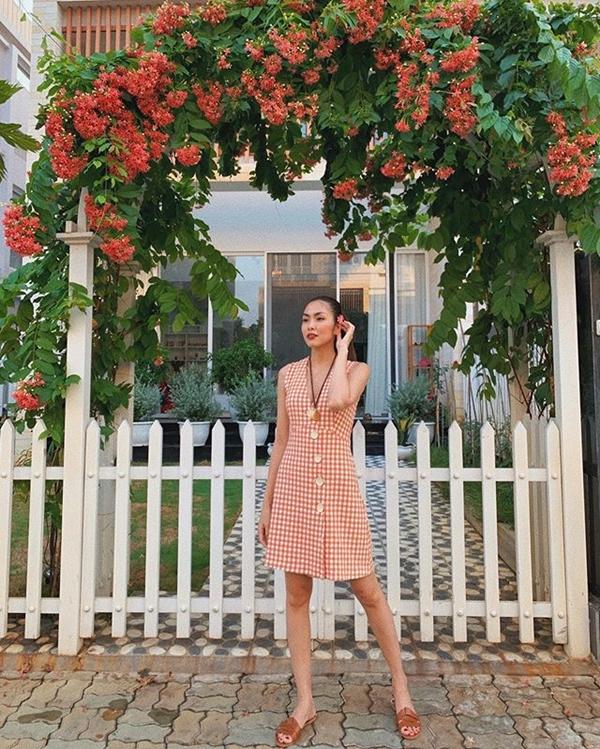 Chiếc váy caro màu cam nhấn nhá chi tiết hàng cúc chạy dọc thân váy giúpTăng Thanh Hà trông rạng rỡ dưới nắng hè.