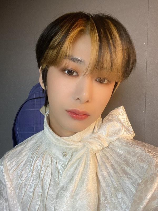 Hyungwoon (Monsta X) như một chàng hoàng tử với bộ trang phục màu trắng cổ cao, kiểu tóc 2 màu nâu và vàng được nhuộm phần mái một cách khéo léo.