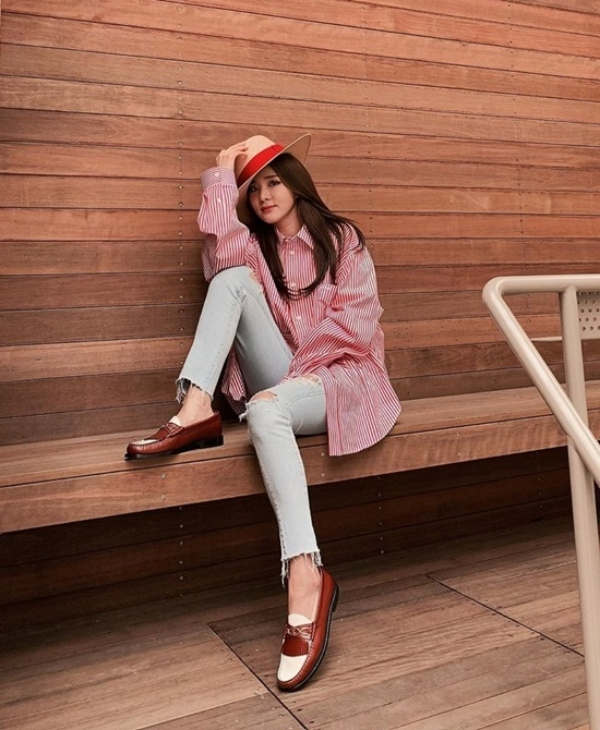Dara trẻ trung với áo sơ mi oversized sọc ca rô đỏ trắng và quần skinny jeans, đôi giày oxford và mũ fedora xuyệt tông.